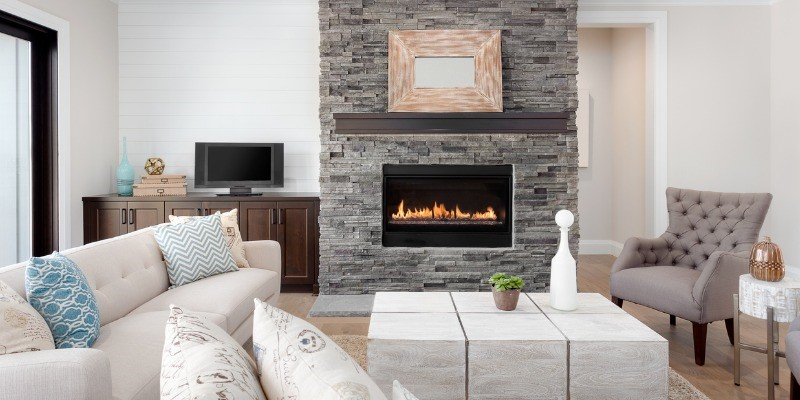 Grey stone fireplace with dark mantel in living room